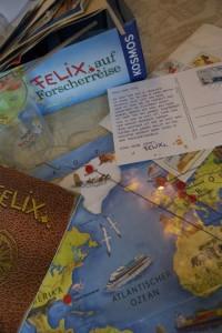 ein Teil des Inhalts vom Experimentierkasten: Forschertagebuch, Weltkarte mit Route, Experimentierbecher, Postkarte, Aufkleber